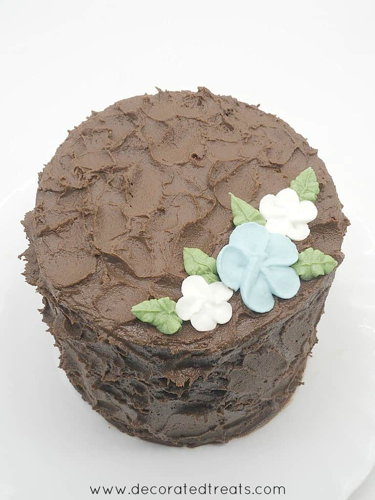 Top view of a chocolate cake covered in chocolate frosting and decorated with royal icing flowers