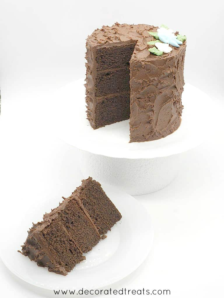 A 3 layer chocolate cake decorating in chocolate frosting and royal icing flowers. A slice of the cake is cut out onto a plate