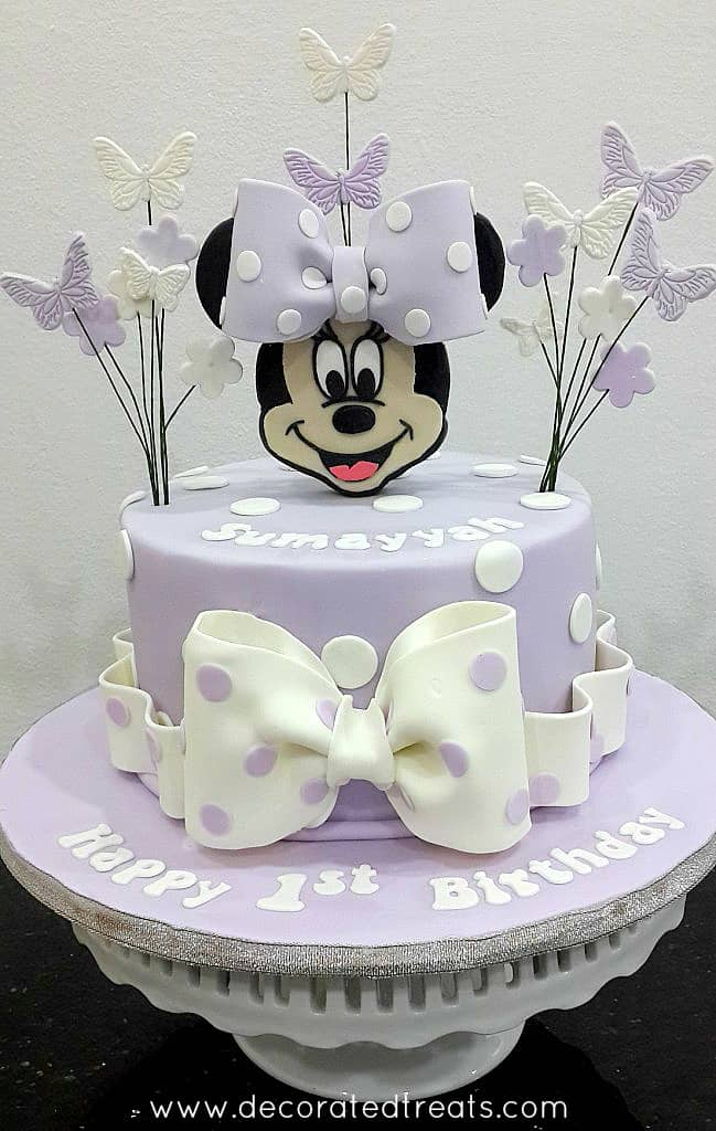 A single tier round purple cake with white polka dots, a Minnie Mouse face topper and butterflies and flowers side toppers. The cake has a large white bow on the front.