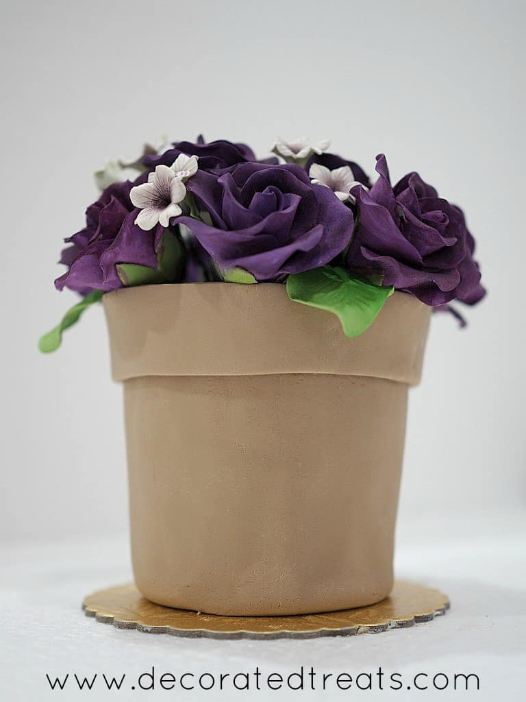 A flower pot shaped cake with purple roses and white filler gum paste flowers