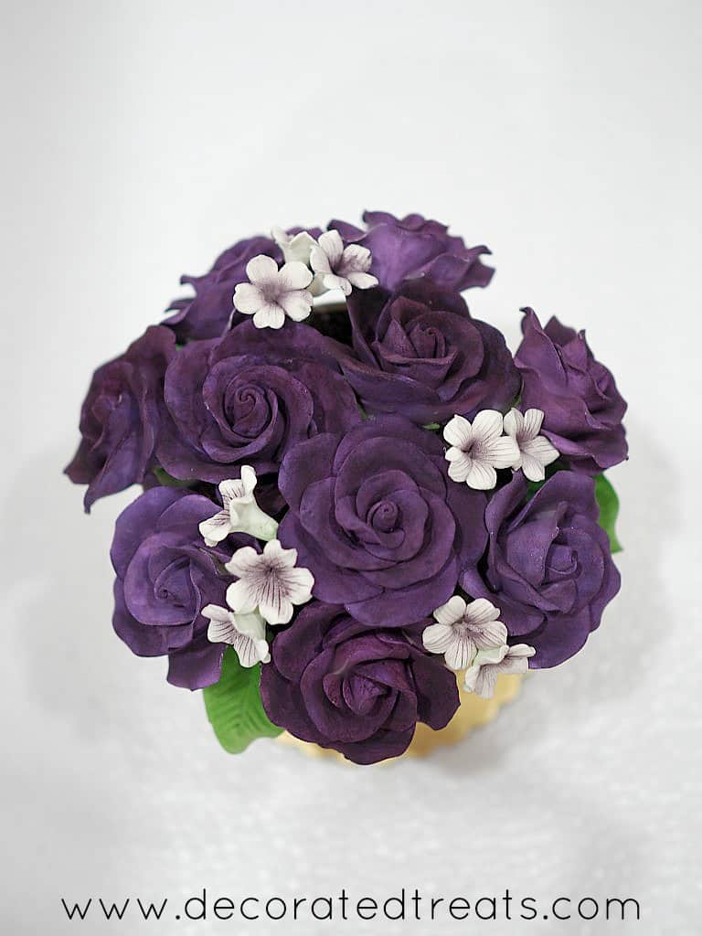 Top view of a flower pot shaped cake with purple roses and white filler gum paste flowers