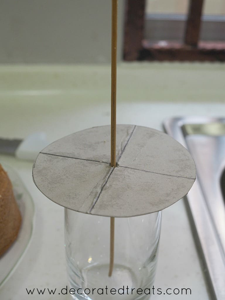 A long skewer through a round cardboard