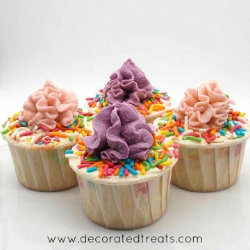4 cupcakes decorated in buttercream and sprinkles