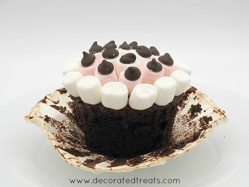 A chocolate cupcake topped with mini marshmallows, with its casing peeled off