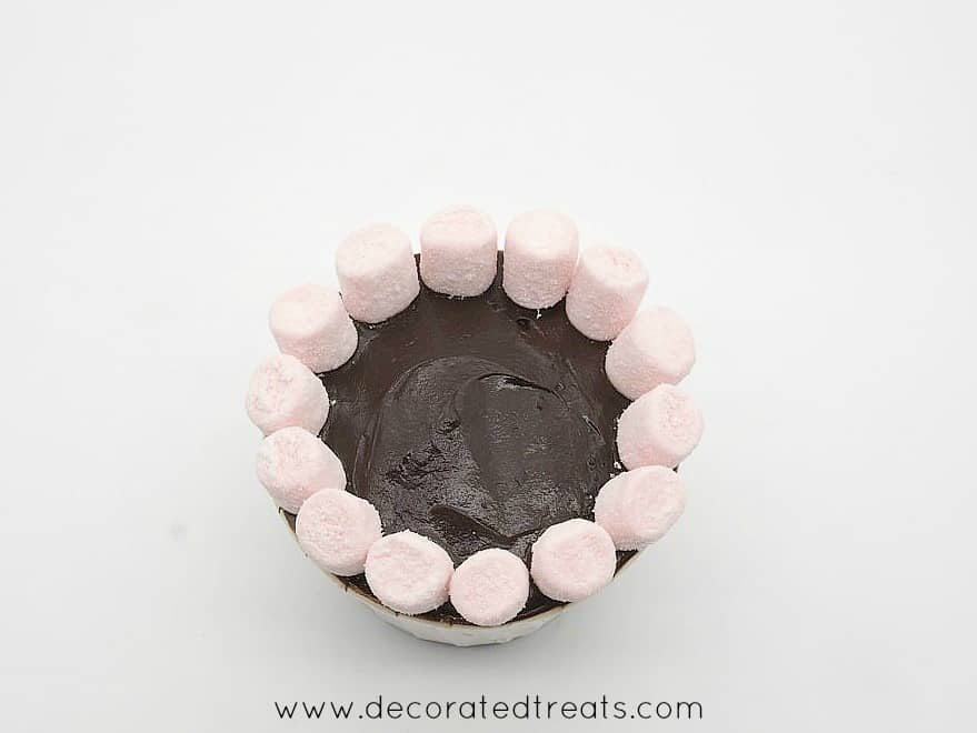 A circle of pink mini marshmallows on a chocolate covered cupcake