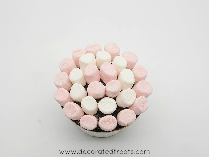 A chocolate cupcake decorated with pink and white mini marshmallows