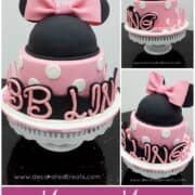 A round pink cake in white polka dots with a Minnie head in black decorated with pink bow