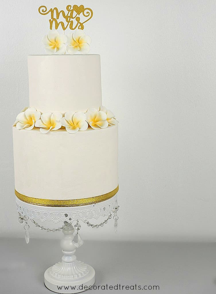 A 2 tier white cake with plumeria flowers and a Mr and Mrs gold topper