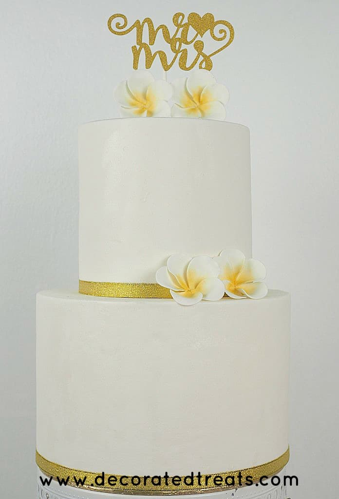 2 gum paste plumeria on the sides and top of cake respectively.
