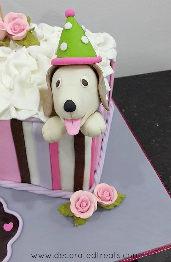 A small dog topper on a square birthday cake