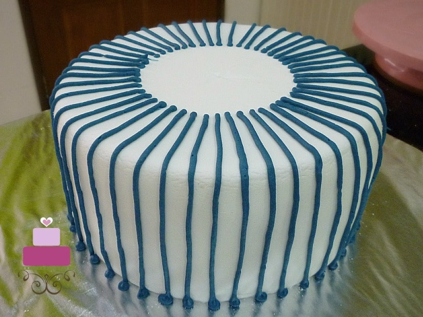 A round white cake with blue strips of icing