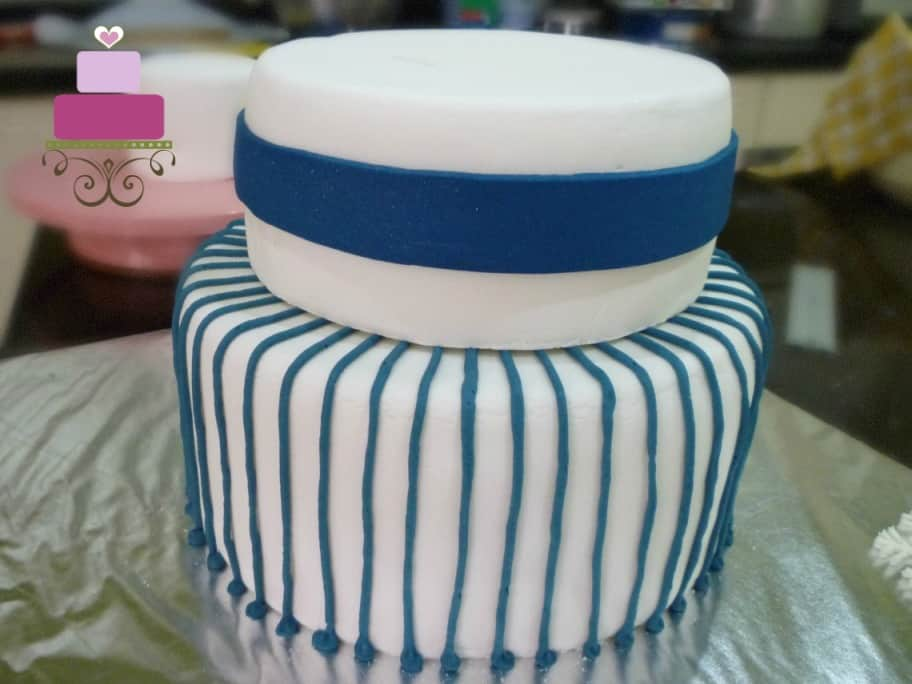 2 tiers of white cake with blue stripes pattern