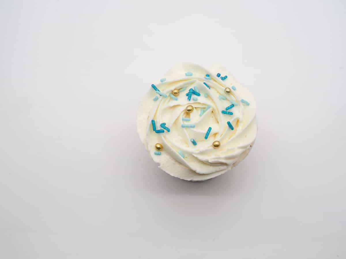 Cupcake with a white buttercream rosette top and blue sprinkles