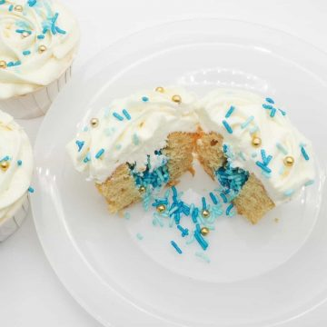 Cupcake cut into half, with the center filled with blue and gold sprinkles