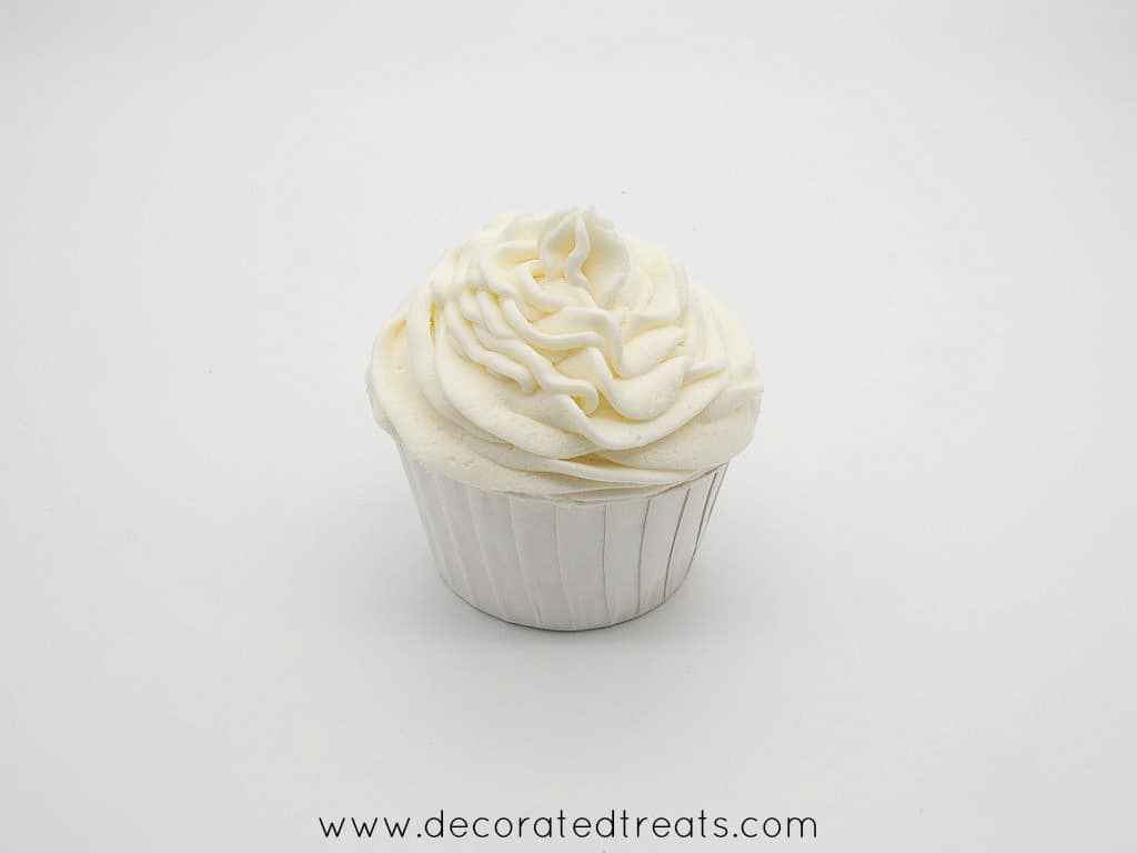 A cupcake topped with buttercream swirl in white