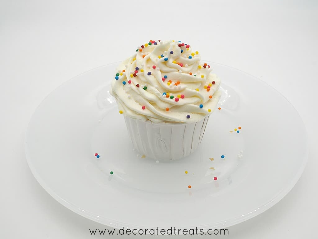 A cupcake in white casing, topped with buttercream and sprinkles