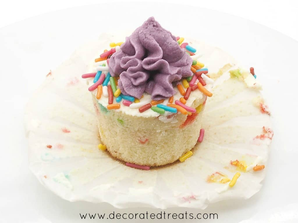 Cupcake decorated with buttercream and sprinkles, with the casing peeled off