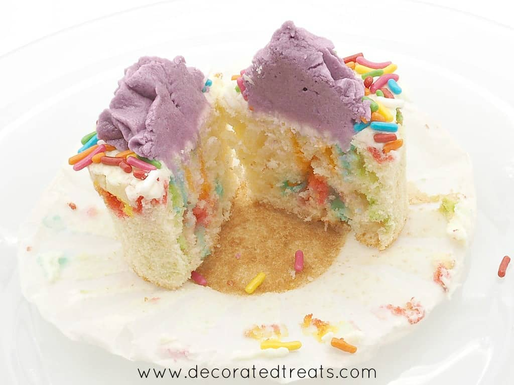 A cupcake with sprinkles and buttercream topping, cut into half