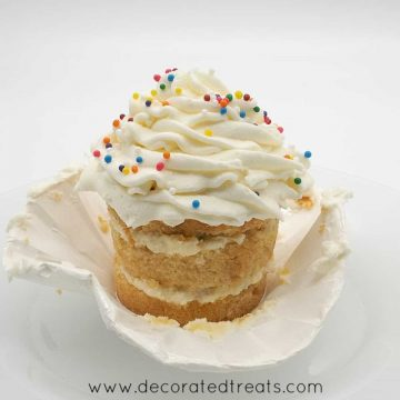 A cupcake with its casing peeled off, and topped with buttercream and sprinkles