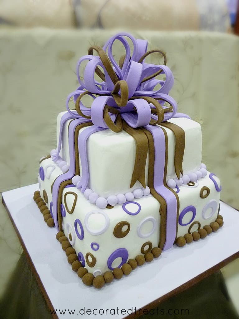 A two tier gift box cake decorated in brown and purple circle cut outs and pretty loop bow