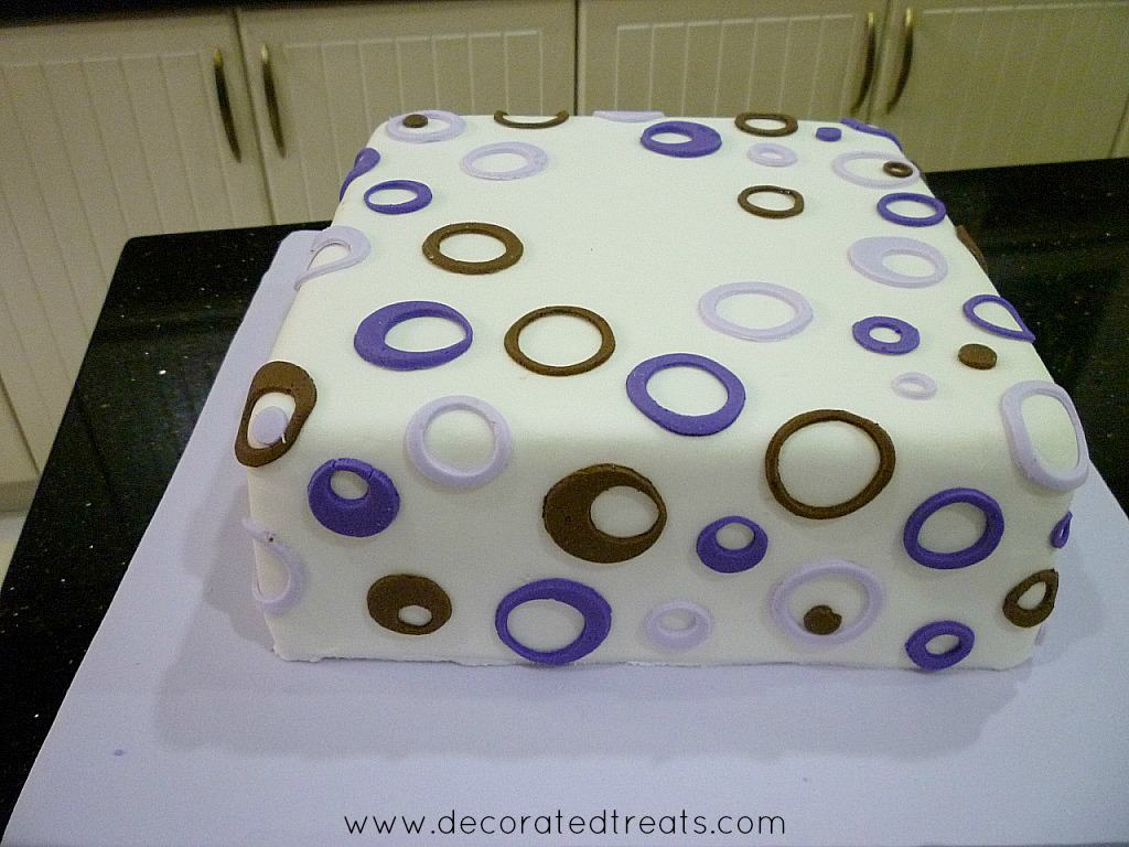 A two tier cake with circle purple and brown cut outs on the bottom tier