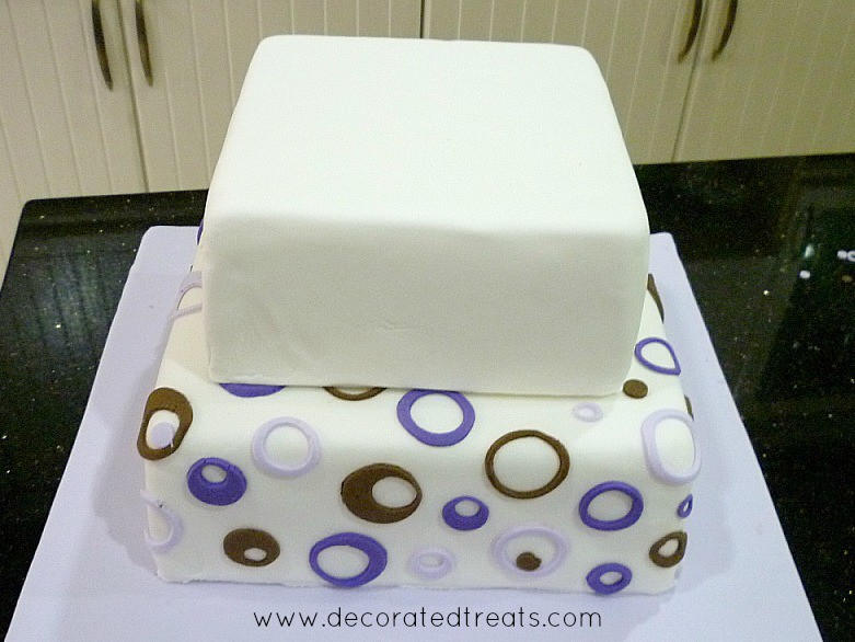 A two tier cake with circle purple and brown cut outs on the bottom tier while the top tier is plain white