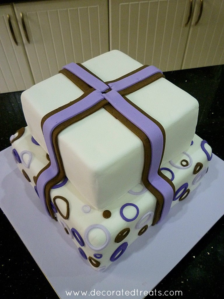 A two tier cake with circle purple and brown cut outs on the bottom tier and fondant strips on the top tier