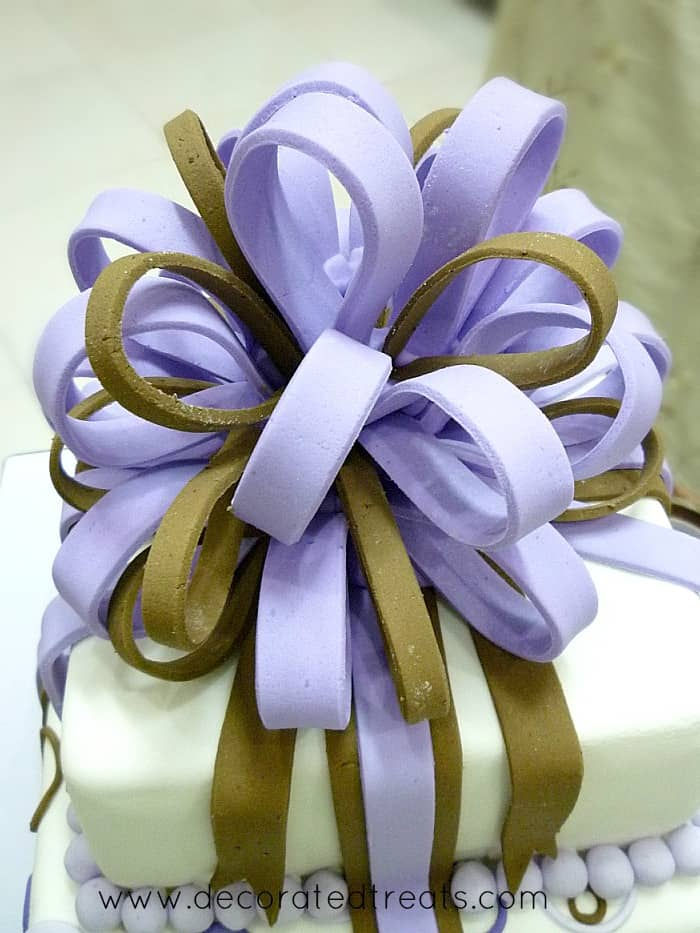 Fondant loop bow in purple and brown on a cake top