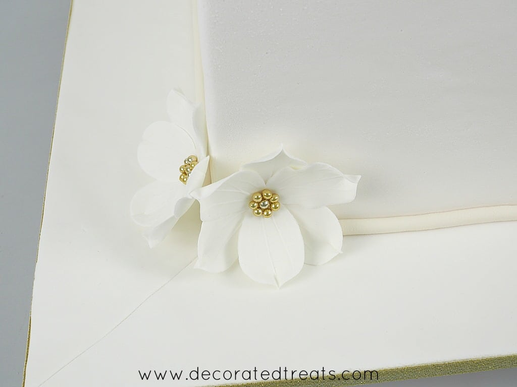 2 gum paste flowers with gold bead centers on the corner of a square cake