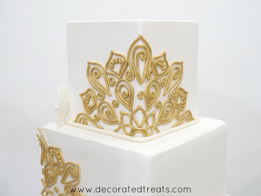 A top tier of a square cake with the sides decorated in gold fondant lace