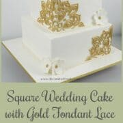 A 3 tier square cake in white fondant and gold lace and white gum paste flowers