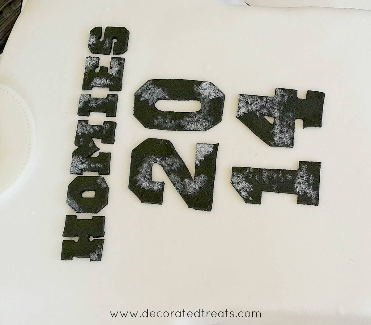 The wordings HOMIES 2014 cut in fondant and placed on a white cake