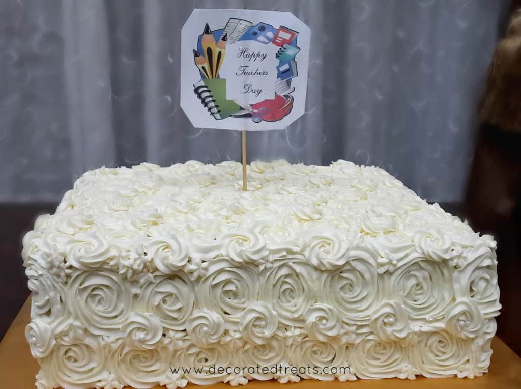 A square cake decorated in white buttercream rosettes and a Teachers Day cake topper
