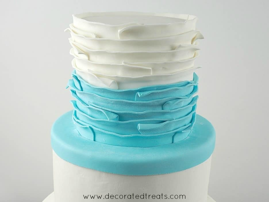 Top tier of a cake covered in white and blue fondant strips