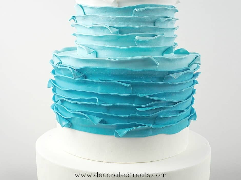Top and second tier of a cake covered in blue fondant strips