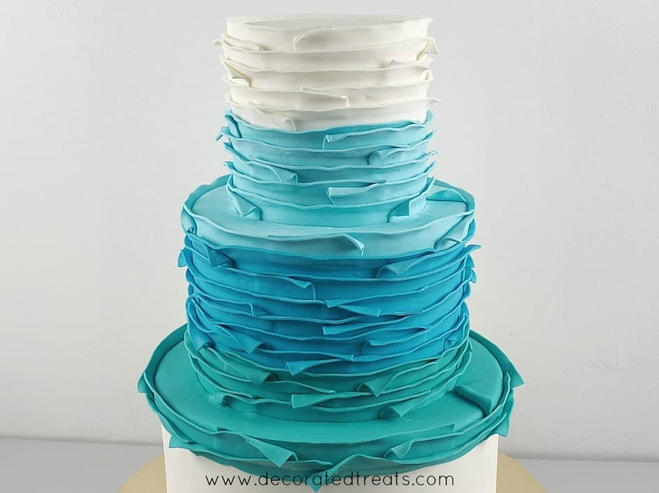 Second tier of a cake covered in blue and turquoise fondant strips
