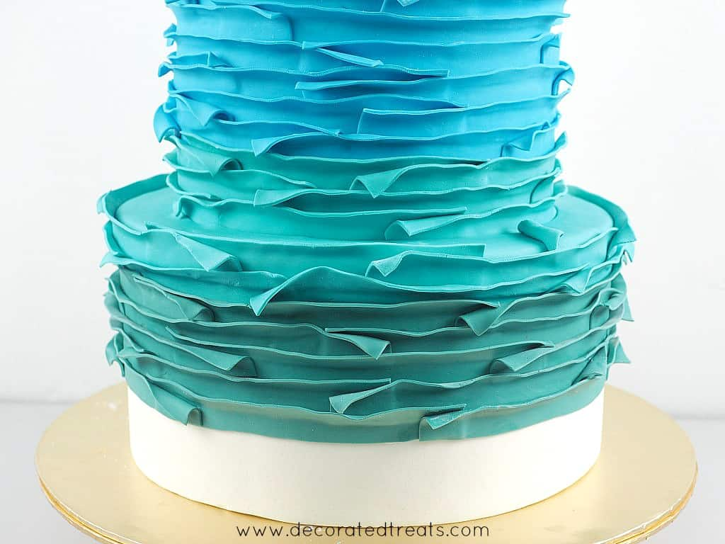 Bottom tier of a cake covered in green fondant strips