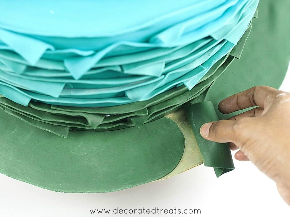 Covering a cake board with green fondant
