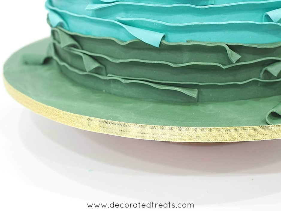 Edges of a cake board with gold ribbon