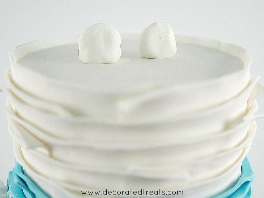 2 lumps of fondant on top of a cake
