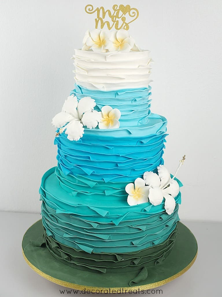 """A 3 tier wedding cake decorated with white, turquoise, blue and green fondant strips and decorated with white plumeria and hibiscus. Cake is topped with a """"Mr & Mrs"""" gold topper"""
