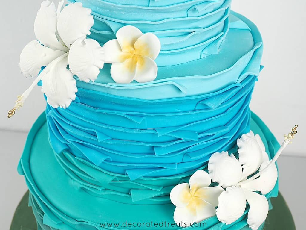 Gum paste hibiscus and plumerias on a blue and green cake