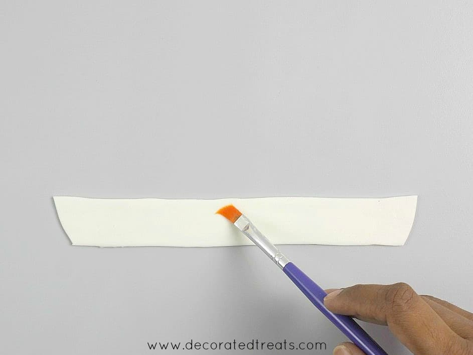 Brush a long white fondant strip