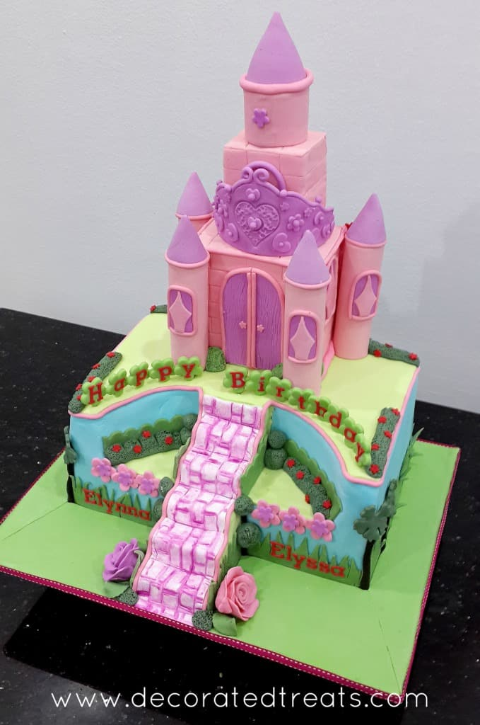 A rectangle cake with a pink castle cake topper