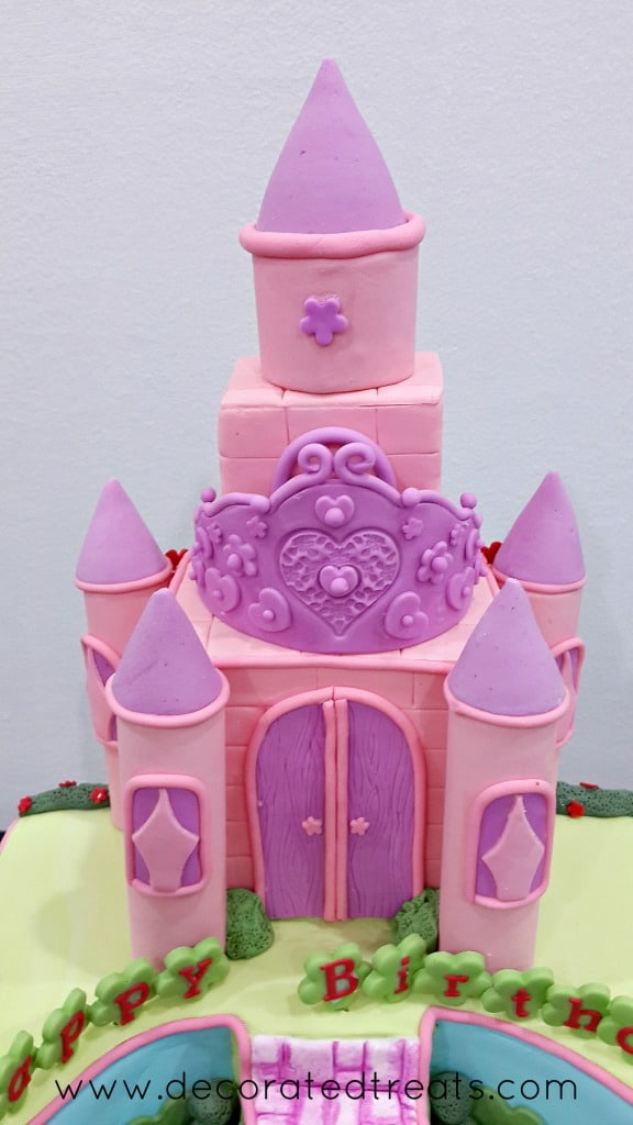 Pink castle cake topper with a tiara on top