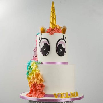 A two tier unicorn came with rainbow colored floral mane and large eyes