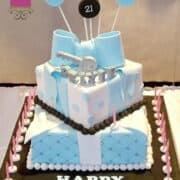 A 2 tier square birthday cake with a large blue bow and silver key topper