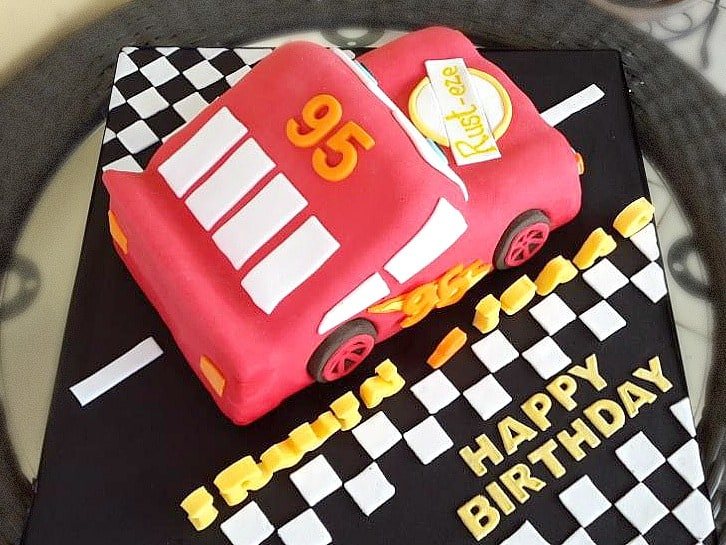 A 3D Lightening Mcqueen cake on a black cake board.