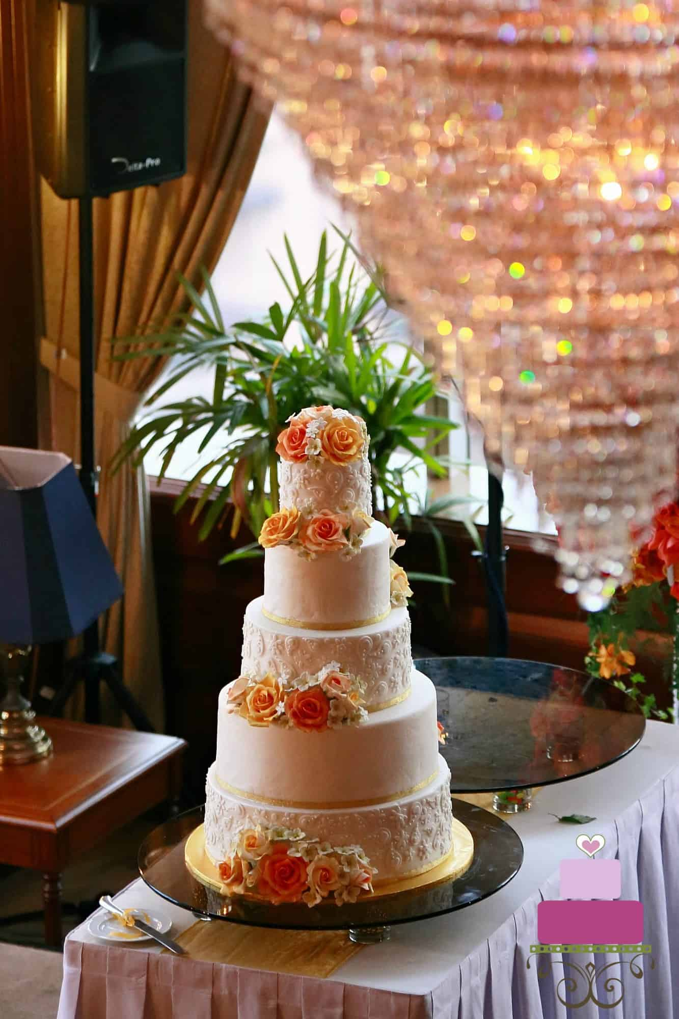 A 5 tier wedding cake decorated with orange and yellow roses and fondant lace