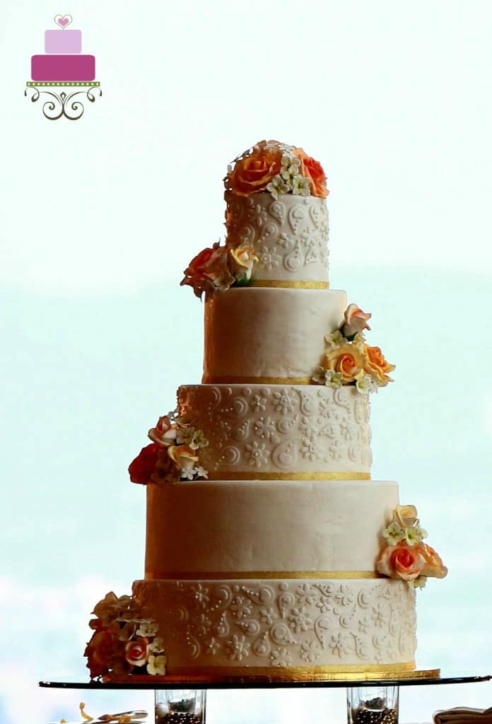 A5 tier wedding cake decorated with orange and yellow roses and fondant lace